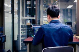 Ein junger Mann arbeitet in Büro mit viel technischer Ausstattung an einem Laptop.