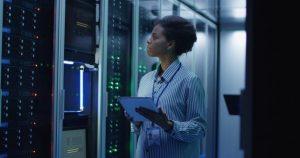 Eine Frau steht in einem modernen Serverraum und überprüft die Computerserver.