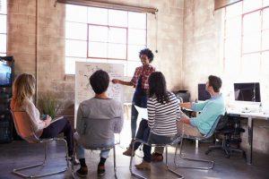 Eine Gruppe von Mitarbeitern steht in einem modernen Büro und überprüft einen Zeitplan auf einem Whiteboard.