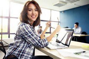 Eine Frau lächelt in die Kamera, während sie in ihrem Büro an einem Laptop arbeitet.