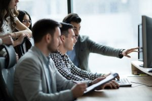 Mehrere junge Kollegen in einem Büro betrachten gemeinsam einen Computerbildschirm.