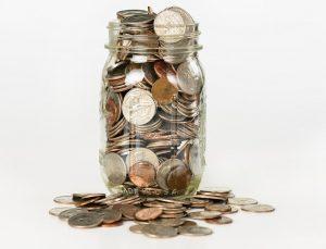 Die Abbildung eines durchsichtigen Glases, das mit Münzen gefüllt ist.