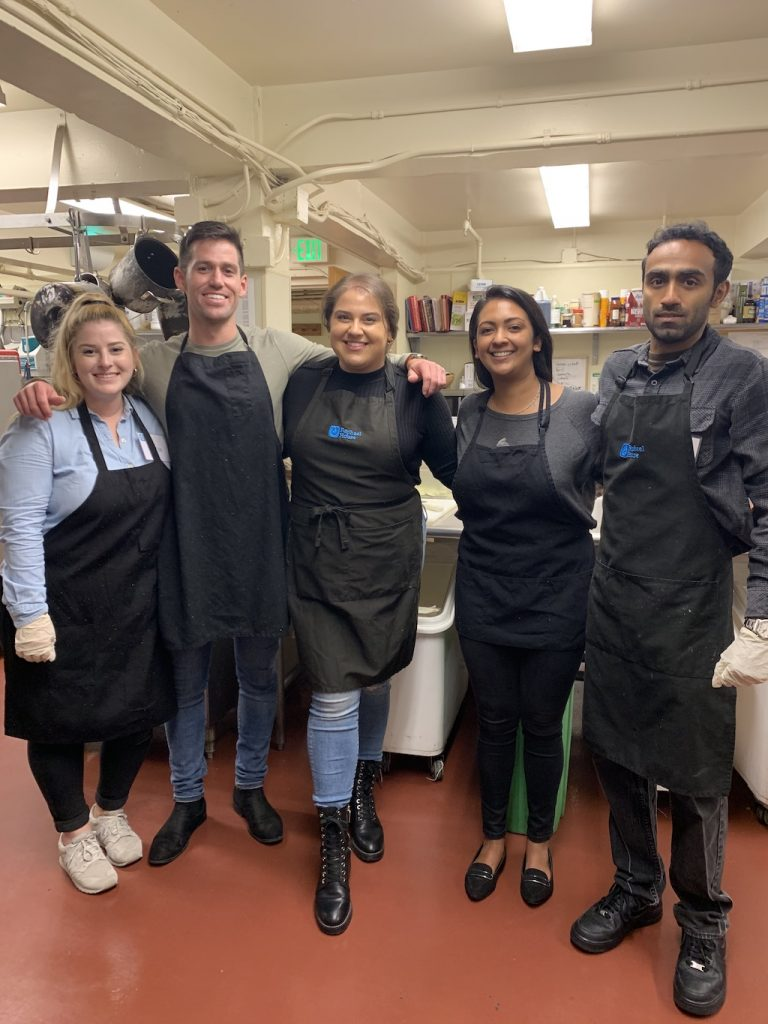 Canto Cares volunteers help prep a meal for families in need at Raphael House