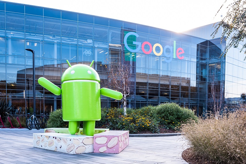 A picture of the Android mascot in front of a Google building.