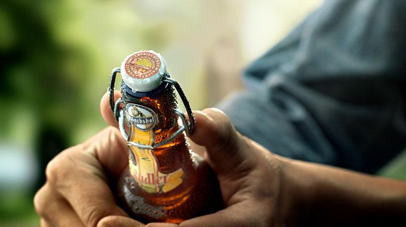 Ein Mann hält eine Flasche.