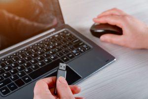 Eine Person bedient mit einer Hand die Maus neben einem Laptop, in der anderen hält sie einen USB-Stick.