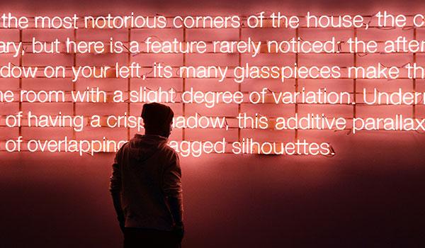 Eine Person betrachtet eine Nachricht, die aus Neonlichtern besteht.