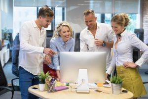 Junge Mitarbeiter in einem Büro, die sich etwas auf einem Bildschirm ansehen.