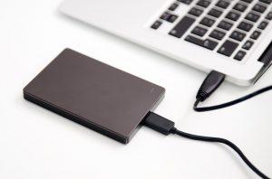 Eine externe Festplatte, die an einen Laptop angeschlossen ist.