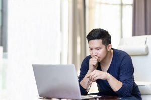Ein junger Mann sitzt vor einem Laptop und betrachtet ihn sehr konzentriert.