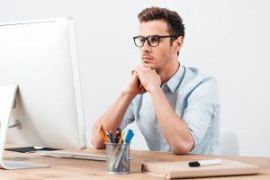 Ein junger Mann mit Brille sitzt an einem Schreibtisch und betrachtet den Bildschirm eines Arbeits-PCs.