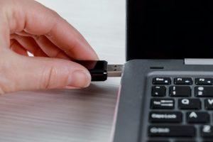 Eine Hand schließt ein Speicherlaufwerk an einen Laptop an.