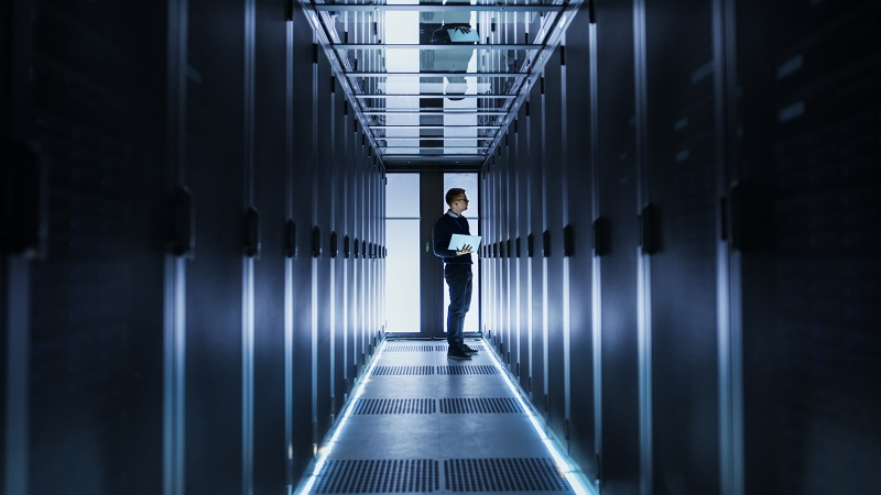 A man checks connections in a large server.