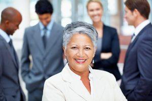 Eine Frau sitzt in einem Meeting zum Thema Content Marketing und lächelt in die Kamera, im Hintergrund unterhalten sich vier Kollegen.