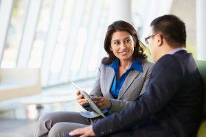 Zwei Mitarbeiter sitzen zusammen und unterhalten sich über die Inhalte von Content Marketing mithilfe eines Tablets.
