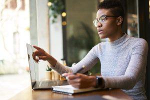 Eine junge Frau mit Brille macht sich Notizen, während sie an einem Laptop arbeitet.