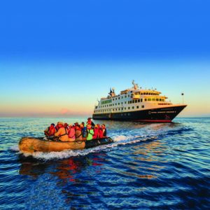 Photo of a cruise ship and passengers on a motor raft.