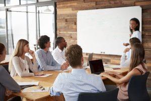 Eine Frau in einem Konferenzraum erklärt dem versammelten Team an einem Whiteboard die Indesign-Grundlagen.