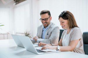 Zwei Kollegen arbeiten freudig mit ihren Laptops am Tisch und lachen miteinander, während sie sich mit den Indesign-Grundlagen beschäftigen.
