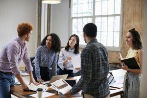 Eine Gruppe junger Mitarbeiter steht um einen Schreibtisch herum und diskutiert die Reputation der Marke.