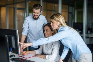Drei junge Mitarbeiter stehen an einem Computer und informieren sich über Markenreputation.