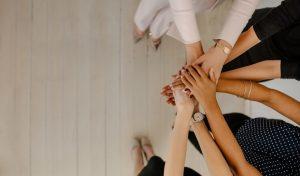 Mehrere Mitarbeiter stehen im Kreis und legen die Hände übereinander, als sie in einem Meeting Vertrauen in die Reputation der Marke aufbauen.