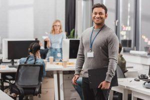 Ein Mann in einem Büro lächelt in die Kamera, während im Hintergrund ein Team an der Wiederherstellung der Markenreputation arbeitet.