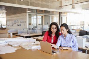 Zwei Mitarbeiterinnen sitzen in einem großen Büro an einem Tisch und arbeiten an einem Laptop.