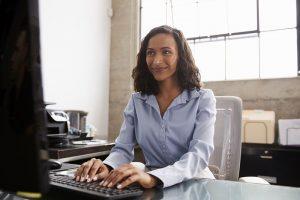 Eine Kollegin sitzt an ihrem Schreibtisch und arbeitet an ihrem Computer.