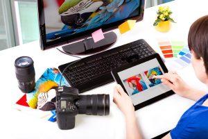 Eine Grafikdesignerin sitzt an einem PC und entscheidet mit einem Tablet, welches Bild sie auswählen soll.