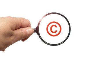 Eine Hand mit einem Vergrößerungsglas, das ein Copyright-Zeichen vergrößert.