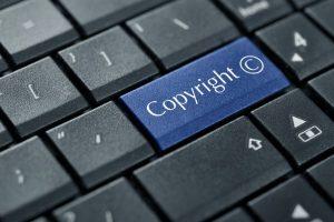 Eine Tastatur, auf der eine Taste blau hervorgehoben ist und das Wort 'Copyright' sowie das Copyright-Zeichen als Aufschrift trägt.