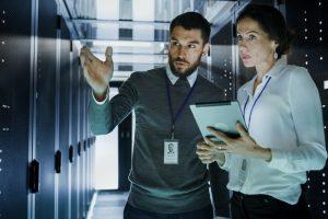 Zwei IT-Mitarbeiter in einem Serverraum unterhalten sich über die optimalen Eigenschaften einer SaaS Medienbibliothek.