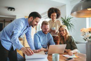Ein Team betrachtet während der gemeinsamen Arbeit den Bildschirm eines Laptops.