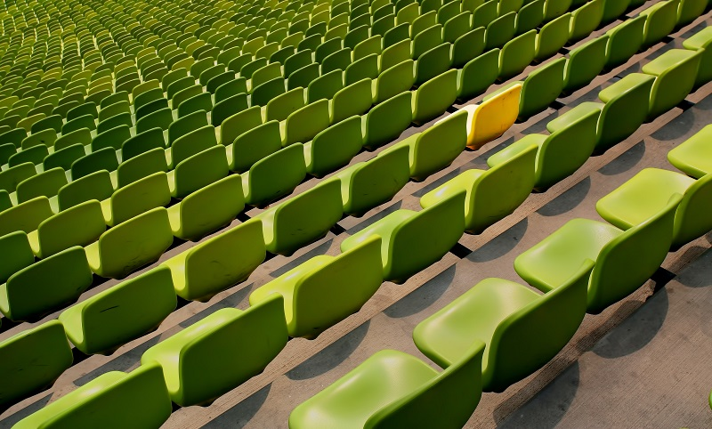 Green seats in a stadium with one yellow.