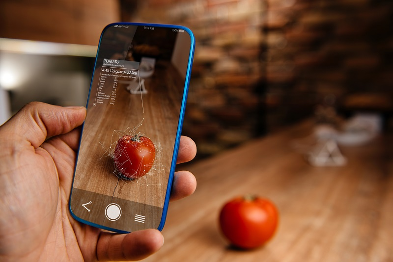 A mobile device taking a photo of a tomato.