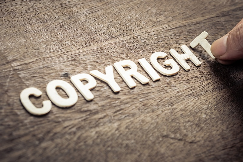 A person putting letter pieces that spell 'copyright'.
