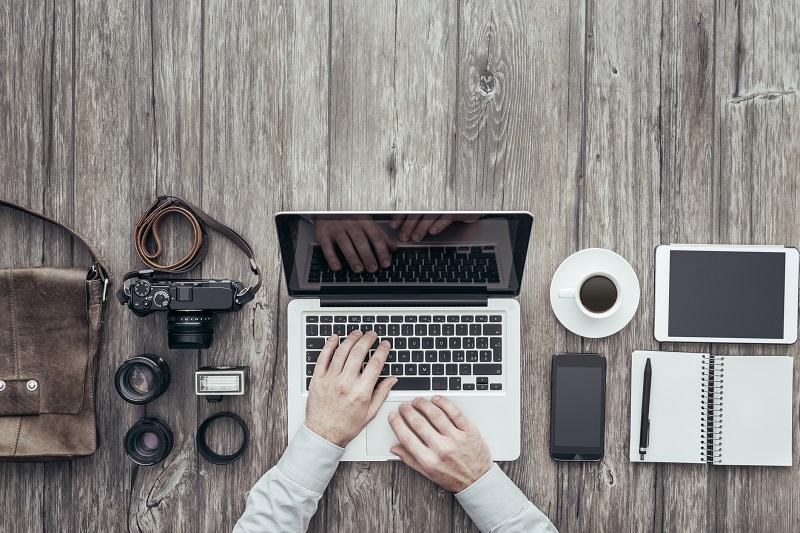 A person uses a laptop alongside a camera.