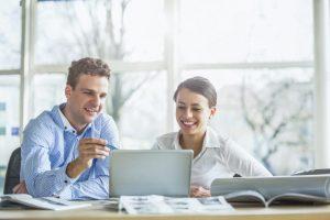 Zwei Kollegen sitzen an einem Tisch und sprechen lächelnd über etwas, das auf einem Laptop vor ihnen zu sehen ist.