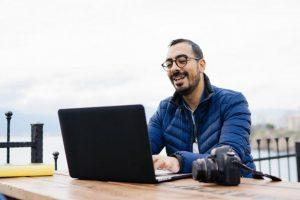 Ein Mann sitzt im Freien an einem Tisch und lächelt über etwas, das auf seinem Laptop-Bildschirm zu sehen ist; neben ihm liegt eine Kamera.
