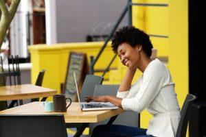 Eine junge Frau arbeitet lächelnd an ihrem Laptop und informiert sich zum PNG Bildformat.