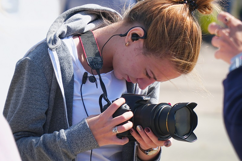 A young woman using a Canon camera.
