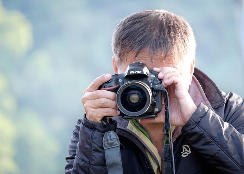 A man takes a photo using a Nikon camera.