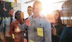 Eine Gruppe von Mitarbeitern bei der Durchsicht von Notizen zum Workflow-Management an einer gläsernen Tafel.