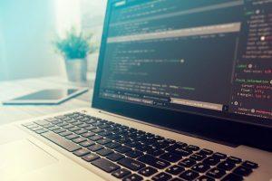 Ein Laptop, auf dem HTML-Code einer Datei im Dokument-Dateityp HTML angezeigt wird.