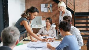 Eine Gruppe von Mitarbeitern diskutiert zum Thema Markenstrategie, während sie um einen mit Papieren bedeckten Tisch herum stehen und sitzen.