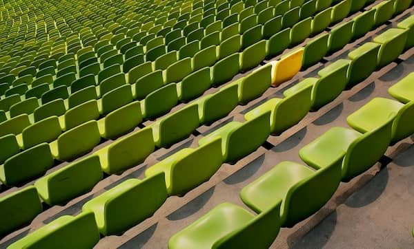 Ein Stadion mit grünen Sitzplätzen und einem gelben Sitz.