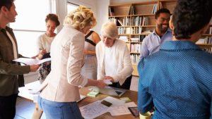 Eine Gruppe von Menschen steht um einen Tisch herum, der mit Papieren bedeckt ist und spricht über das Thema Markenstrategie.