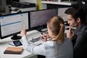 Zwei Mitarbeiter in einem Büro diskutieren über den Code einer Webseite, der auf einem Computerbildschirm vor ihnen angezeigt wird.