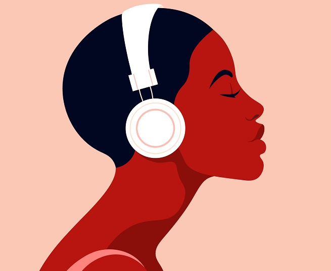 A woman listens to headphones.